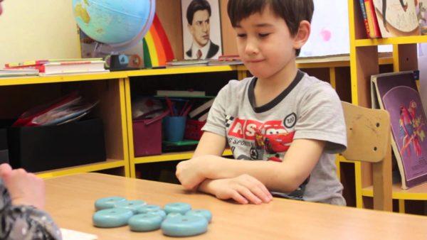 Мальчик сидит за столом и смотрит на круглые элементы пирамидки