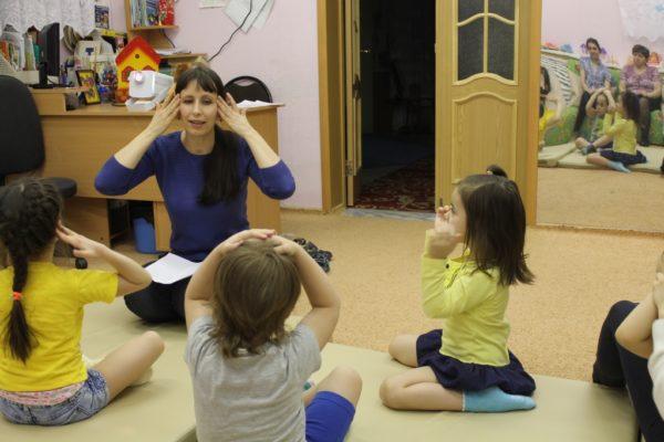 Педагог показывает упражнение детям, сидящим на коврике