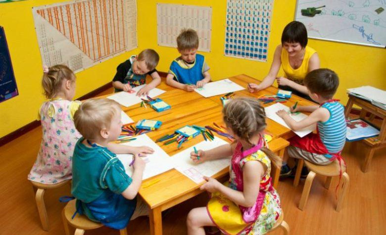 Дети с педагогом рисуют за столом