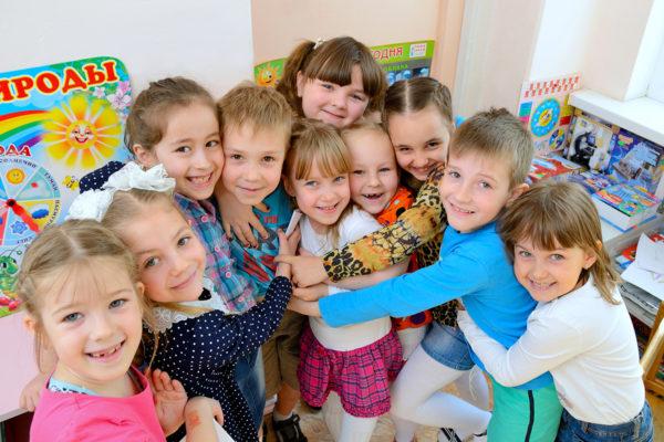 Дети обнимают друг друга в уголке природы