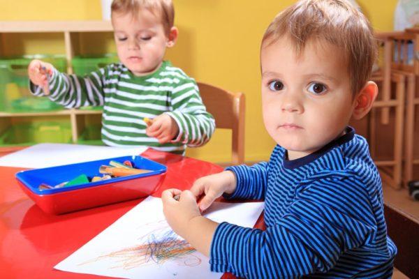 Два мальчика рисуют карандашами