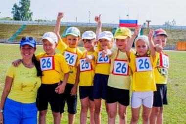 Педагог и дети в жёлтых футболках на стадионе