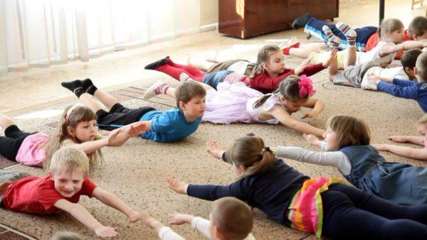 Дети лёжа выполняют зарядку