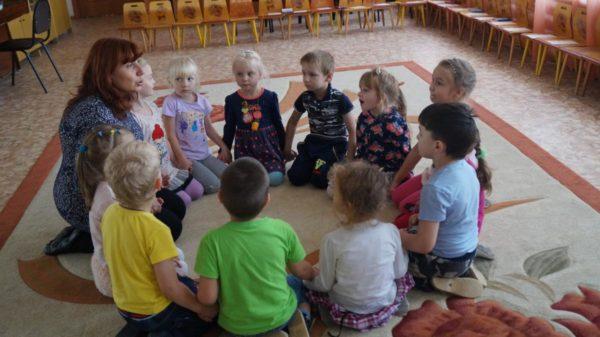 Дети с педагогом сидят на коврике