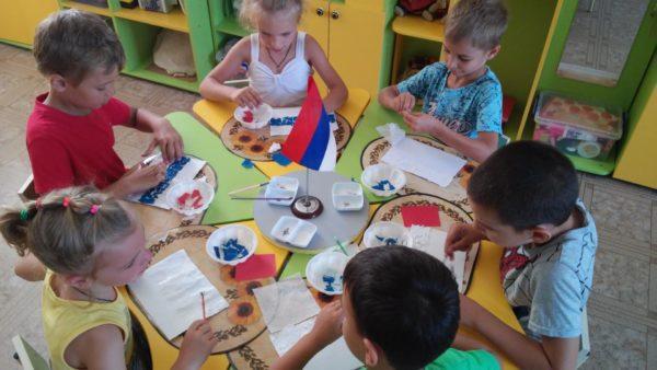 Дети сидят за столом и выполняют аппликацию Флаг России