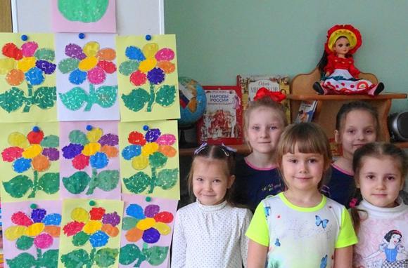 Девочки стоят рядом со стендом с аппликациями цветов
