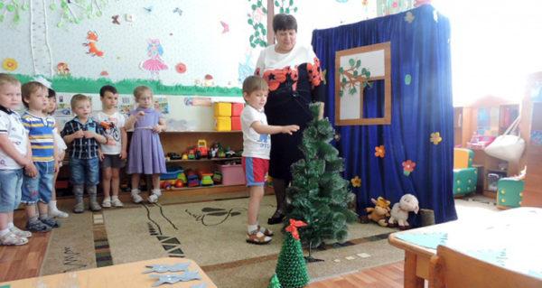 Ребёнок возле искусственной ёлки в детском саду