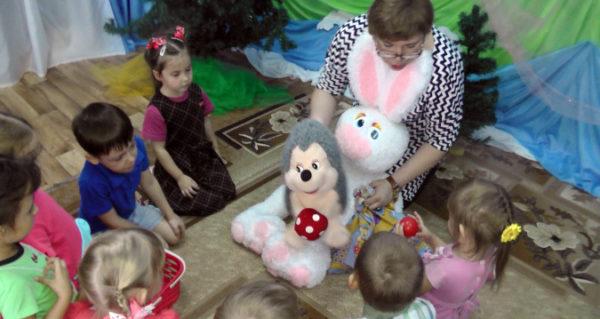 Воспитатель показывает детям игрушечного зайца и ёжика