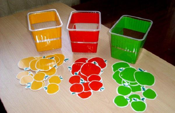 Коробочки трёх цветов и игрушечные яблоки таких же цветов