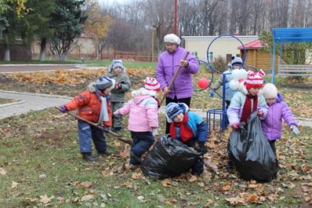 Дети и воспитатель убирают листья