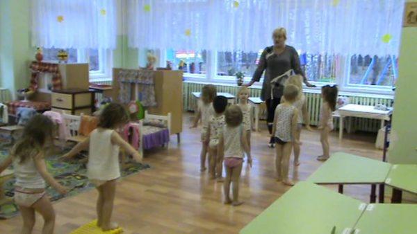 Воспитательница проводит гимнастику после сна с детьми, одетыми в трусы и майки