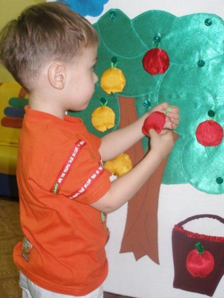 Мальчик вешает на дерево игрушечное яблоко