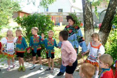 Воспитательница в костюме со шляпой с дети в национальных костюмах