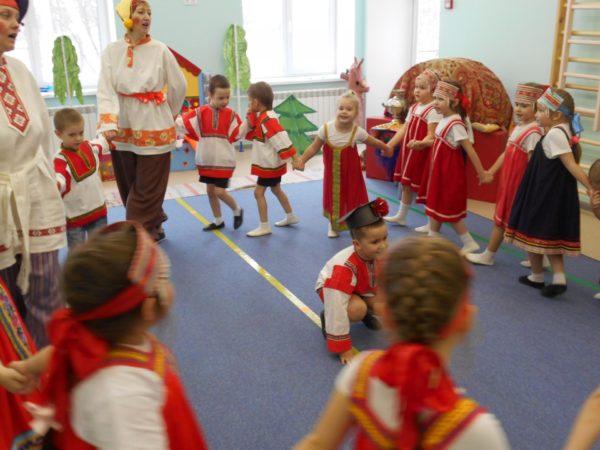 Два воспитателя и дети в национальных костюмах в хороводе