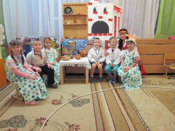 Дети с воспитателем сидят на стульях вокруг самовара