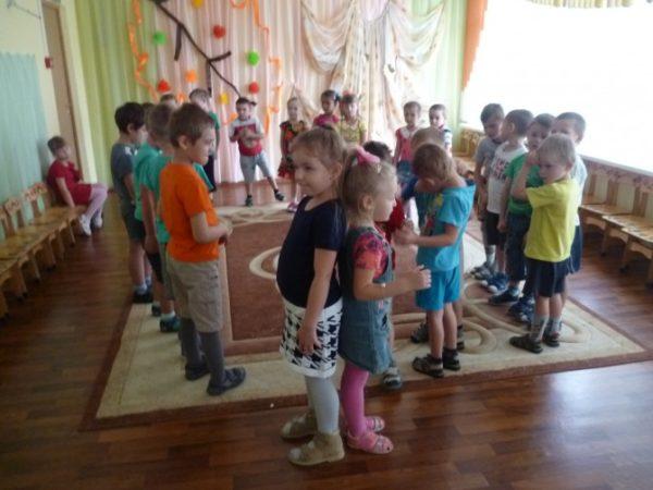 На первом плане стоят мальчик с девочкой спинами друг к другу, на заднем — дети в кругу