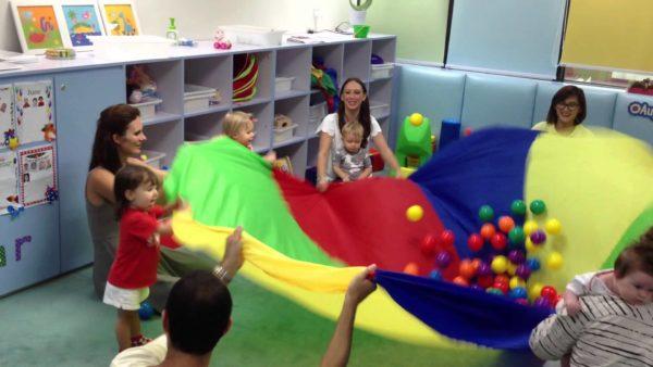 Дети подкидывают мячики на покрывале-парашюте