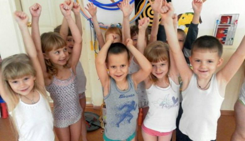 Дети в маечках стоят, подняв руки вверх