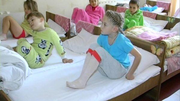 Дети в пижамах сидят в кроватках