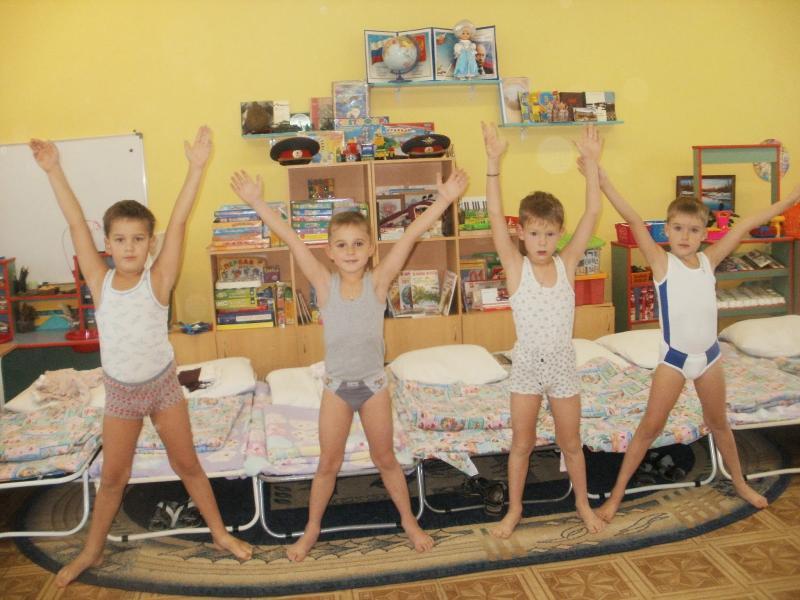 Четыре мальчика стоят после сна, держат руки вверх