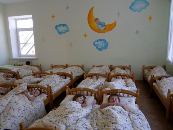 Дети спят в кроватках, на стене аппликация луны