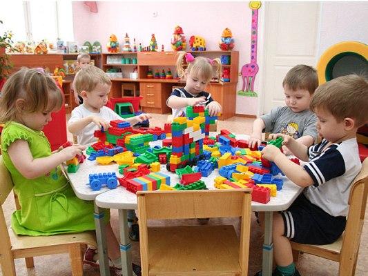 Дети сидят за столом, играют с конструктором