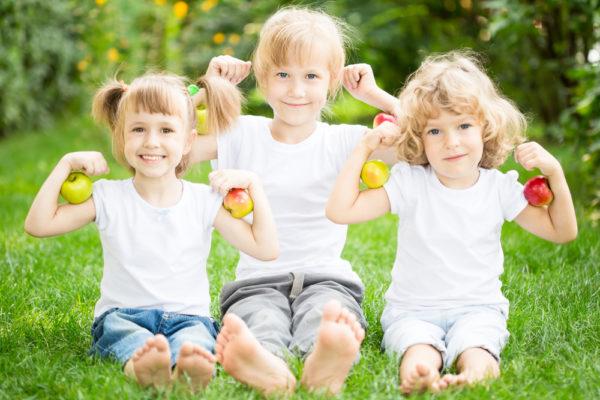 Дети держат яблоки и улыбаются