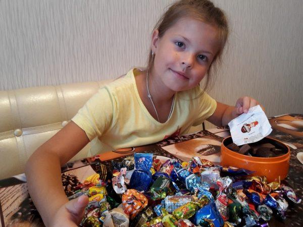 Девочка сидит за столом с грудой конфет