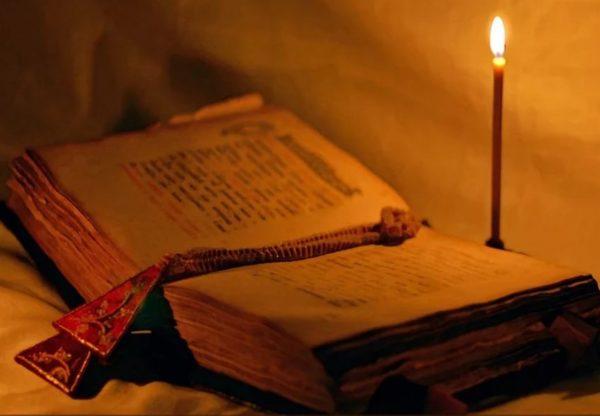 Открытая старинная книга и горящая свеча
