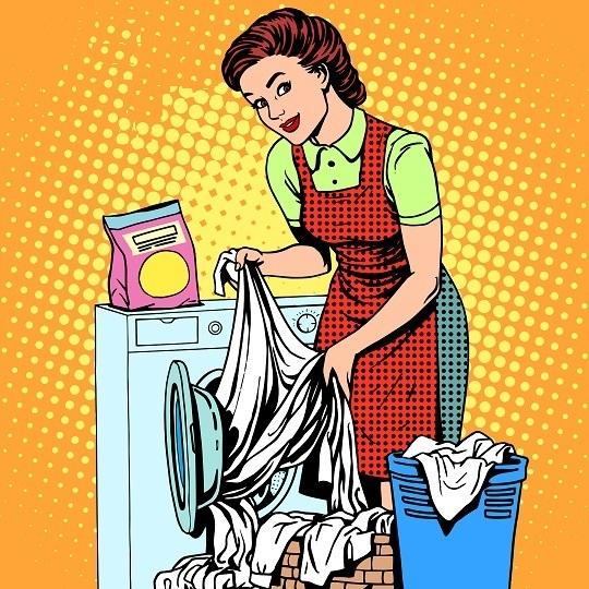 Женщина закладывает бельё в стиральную машинку