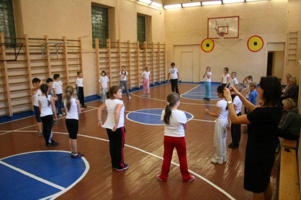 Школьники играют в подвижную игру в спортивном зале