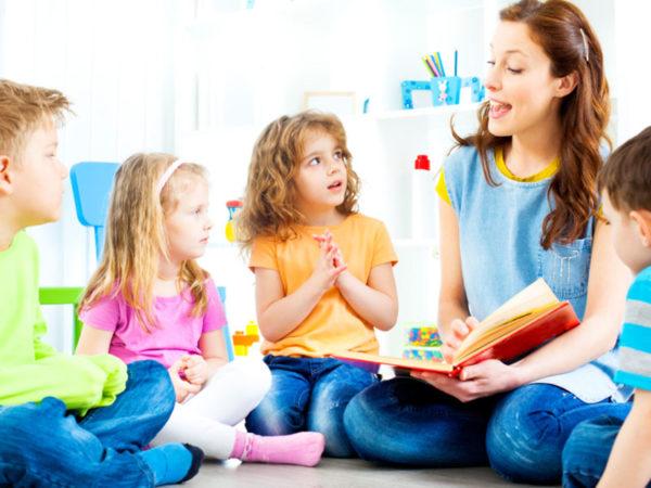 Дети сидят на полу и увлечённо слушают педагога
