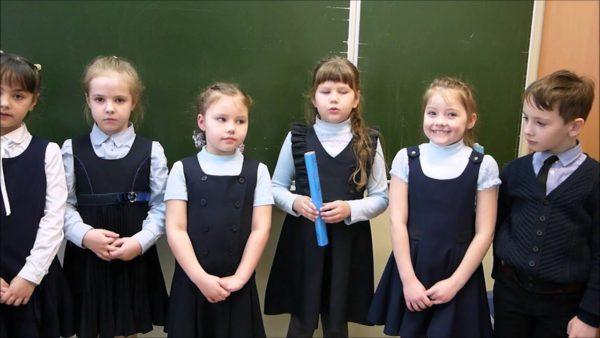 Шестеро детей в школьной форме стоят у доски