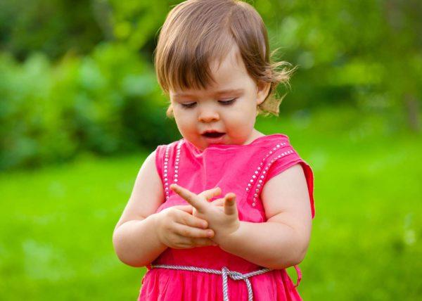 Маленькая девочка считает, загибая пальчики