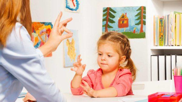 Девочка и мама играют в пальчиковую игру