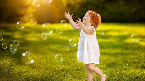 Девочка ловит мыльные пузыри