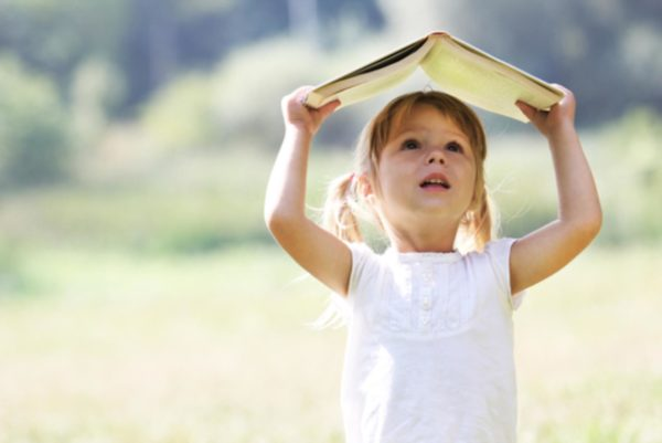 Девочка стоит, держа книгу над головой