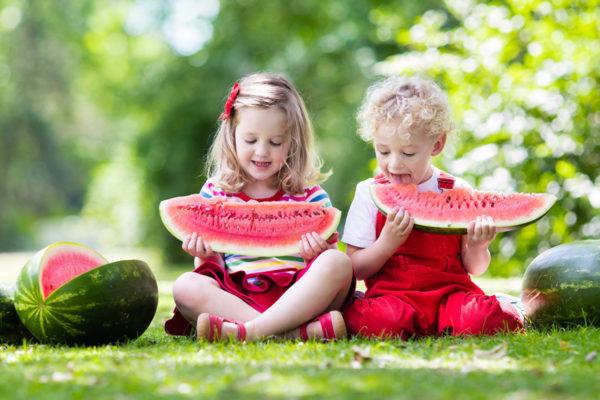Двое детей едят арбуз