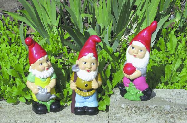 Три фигурки гномов рядом с клумбой