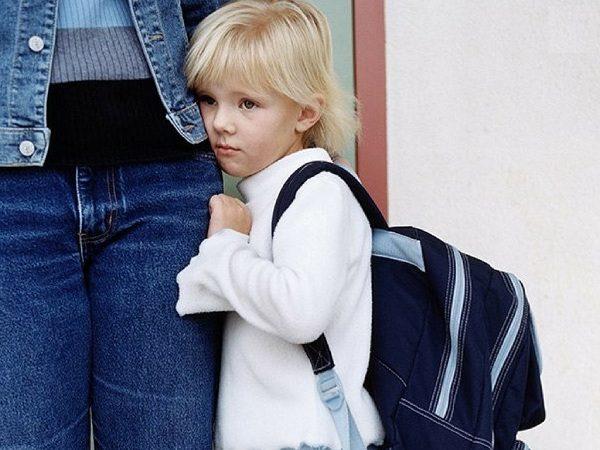Мальчик с портфелем за спиной прижался к ноге мамы