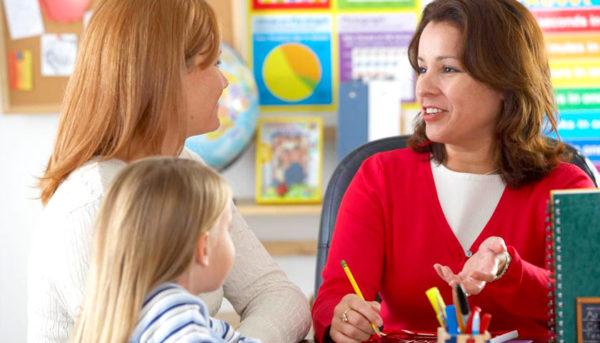 Мама девочки разговаривает с воспитателем