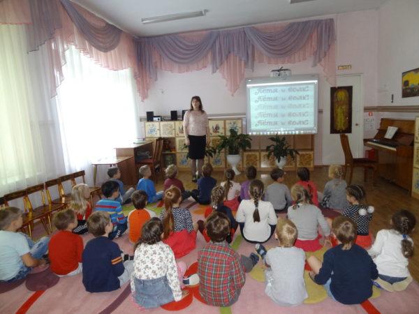 Группа детей сидит на полу, смотрит на мультимедийный экран и слушает педагога