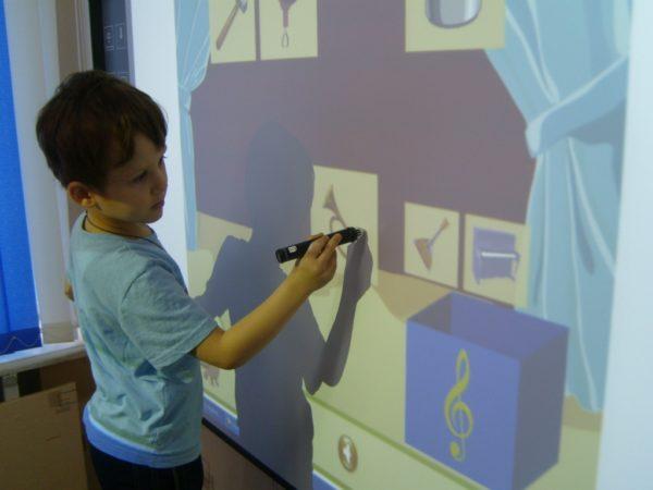Мальчик выполняет задание на интерактивной доске с изображениями музыкальных инструментов