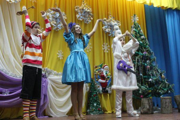 Буратино, Мальвина и Пьеро стоят на сцене у новогодней ёлки