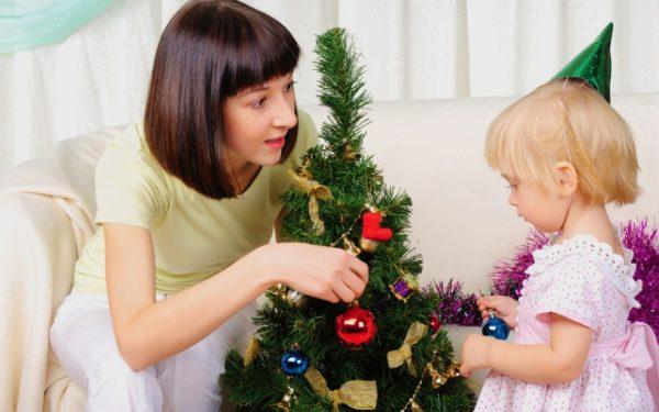 Мама с маленькой дочкой украшают новогоднюю ёлку