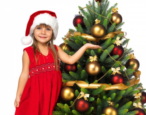 Маленькая девочка возле украшенной ёлки