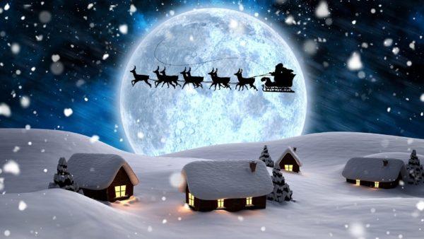 Дед Мороз летит по небу в повозке с оленями