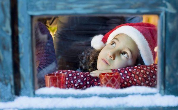 Девочка в новогоднем колпачке задумчиво смотрит в окно
