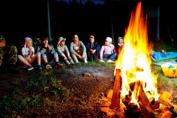 Дети сидят у костра в лагере