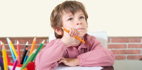 Мальчик задумался, держа в руке карандаш